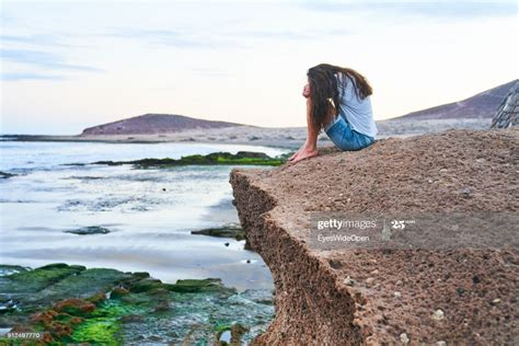 Woman sitting alone on the rocks at the beach on January